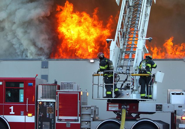 Firefighters fight a two-alarm fire at Southtowne Lanes in Eugene, Ore. Wednesday, August 5, 2015. (Photo by Brian Davies/The Register-Guard via AP Photo)