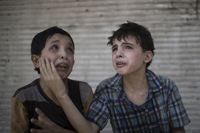 Zeid Ali, 12, left, and Hodayfa Ali, 11, comfort each other after their house was hit and collapsed during fighting between Iraqi forces and Islamic State militants in Mosul, Iraq, Saturday, June 24, 2017. The Ali cousins said some of their family members are still under the rubble. (Photo by Felipe Dana/AP Photo)