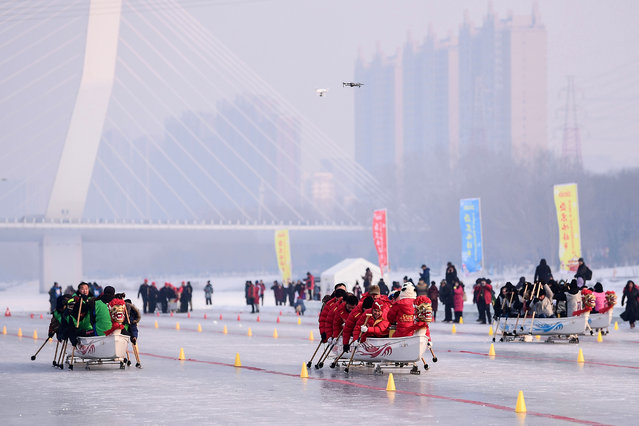 Teams compete during a dragonboat on ice competition in Shenyang in China's northeastern Liaoning province on January 3, 2020. (Photo by AFP Photo/China Stringer Network)