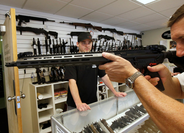"""A prospective buyer examines an AR-15 as salesman Ryan Martinex watches at the """"Ready Gunner"""" gun store in Provo, Utah, U.S., June 21, 2016. (Photo by George Frey/Reuters)"""