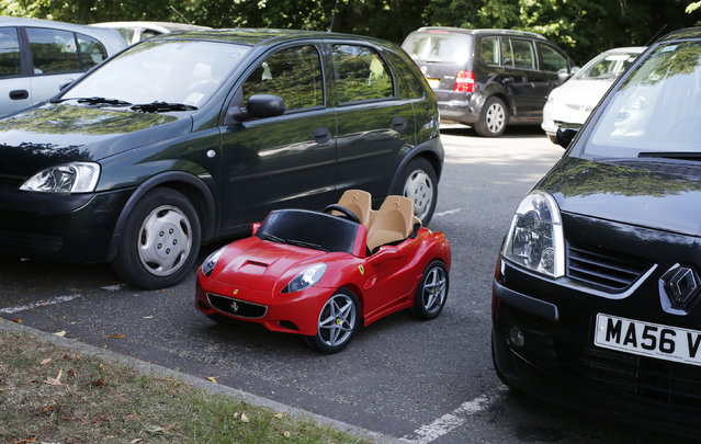 A child's toy Ferrari is parked between two hatchbacks at the Hale Barns Cricket Club in Altrincham, Cheshire, northern England June 19, 2013. (Photo by Phil Noble/Reuters)