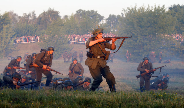 Military enthusiasts dressed as Nazi troops take part in a re-enactment of a World War II battle at the Hero fortress as they mark the 75th anniversary of the Nazi Germany invasion, in Brest, Belarus June 22, 2016. (Photo by Vasily Fedosenko/Reuters)