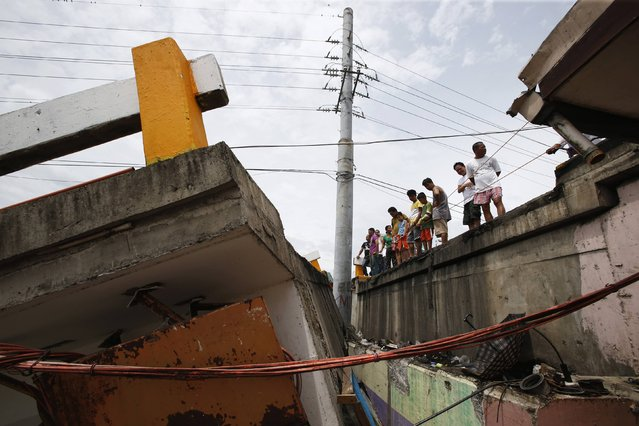 Residents stand on the edge of a road next to a bridge destroyed during the onslaught of Typhoon Rammasun, (locally named Glenda) in Batangas city south of Manila, July 17, 2014. The Philippines set to work clearing debris, reconnecting power and rebuilding flattened houses on Thursday after a typhoon swept across the country killing 38 people, with at least eight missing, rescue officials said. (Photo by Erik De Castro/Reuters)
