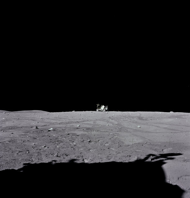 "Astronaut John W. Young, Apollo 16 mission commander, drives the ""Rover"", Lunar Roving Vehicle (LRV) to its final parking place near the end of the third extravehicular activity (EVA-3) at the Descartes landing site. Astronaut Charles M. Duke Jr., Lunar Module pilot, took this photograph looking southward. The flank of Stone Mountain can be seen on the horizon at left. The shadow of the Lunar Module ""Orion"" is visible in the foreground. (Photo by NASA)"