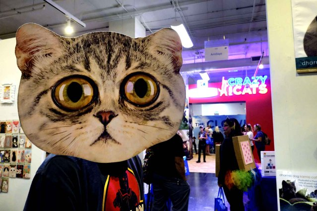 Jean-Pierre Giagnoli walks through a crowded area of vendors hawking cat related goods at CatCon LA in Los Angeles, on Sunday, June 26, 2016. (Photo by Richard Vogel/AP Photo)