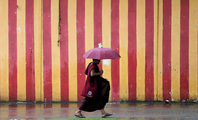 A Buddhist monk walks in the rain during a wet day in Colombo, Sri Lanka on September 25, 2019. (Photo by Dinuka Liyanawatte/Reuters)