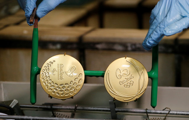 A worker from the Casa da Moeda do Brasil (Brazilian Mint) takes out gold-plated Rio 2016 Olympic and Paralympic medals in Rio de Janeiro, Brazil, June 28, 2016. (Photo by Sergio Moraes/Reuters)
