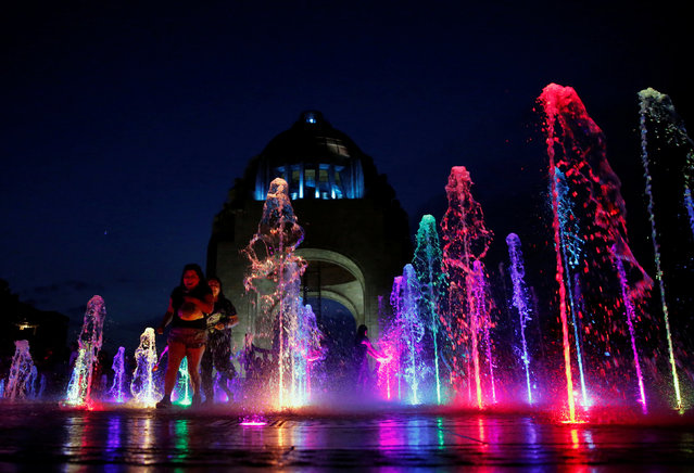 People are seen by an illuminated fountain at the Monument of the Revolution in Mexico City, Mexico on August 5, 2017. (Photo by Henry Romero/Reuters)