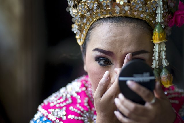 A thai classical dancer touches up her makeup before performing at the Erawan shrine, the site of Monday's deadly blast, in central Bangkok, Thailand, August 21, 2015. (Photo by Athit Perawongmetha/Reuters)