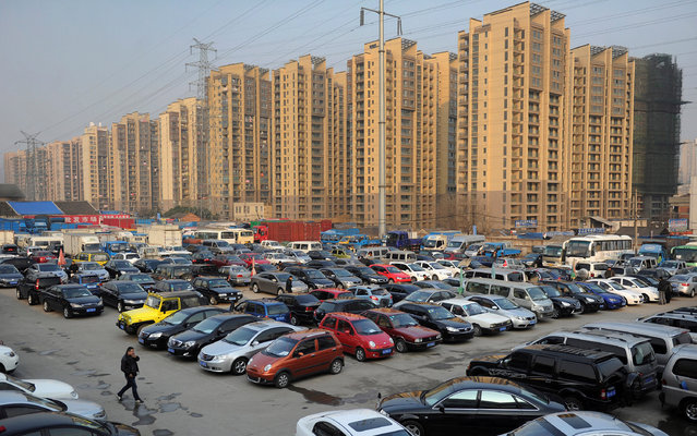 Car dealers and customers walk at a second-hand car market near a newly-built residential area in Hefei, Anhui province, China January 26, 2013. (Photo by Reuters/Stringer)