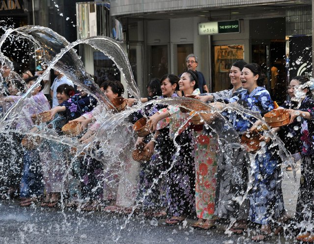 "People dressed in ""yukatas"", or cotton summer kimonos, splash water onto the ground along a street in the shopping area of Ginza in Tokyo on August 3, 2014. Hundreds of yukata-clad people participated in the annual summer event to cool off as Tokyo's temperatures soared over 35 degree Celsius (95 F). (Photo by Yoshikazu Tsuno/AFP Photo)"