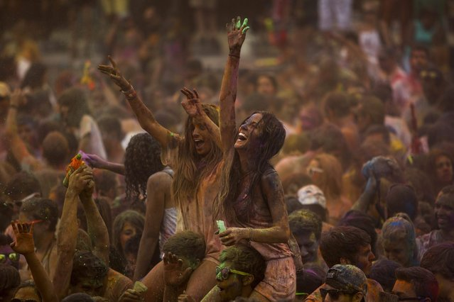 Revelers dance after throwing special colored powders on each other during a Monsoon Holi Festival in Madrid, Spain, Saturday, August 9, 2014. The festival is based on the Hindu spring festival Holi, also known as the festival of colors where participants color each other with dry powder and colored water. (Photo by Andres Kudacki/AP Photo)