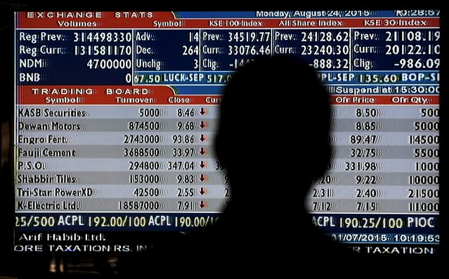 A man is silhouetted as he monitors stock prices during a trading session in the halls of Karachi Stock Exchange, Pakistan, August 24, 2015. (Photo by Akhtar Soomro/Reuters)
