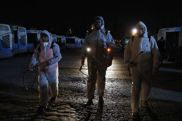 Workers wearing protective suits walk at a bus depot before they spray disinfectant inside the vehicles in Athens, Saturday, March 14, 2020. Greece has announced new sweeping closures Friday, closing all shopping malls, cafes, bars and restaurants, except those that provide only take-aways or deliveries. All museums, ancient sites, libraries and beauty salons will also shut down. For most people, the new coronavirus causes only mild or moderate symptoms, such as fever and cough. For some, especially older adults and people with existing health problems, it can cause more severe illness, including pneumonia. (Photo by Thanassis Stavrakis/AP Photo)
