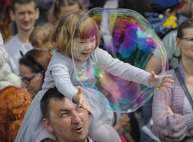 A child reaches for a soap bubble during the Global Bubble Parade in Bucharest, Romania, Sunday, May 5, 2019. Dozens took part in the Global Bubble Parade, an international event, held in 125 cities across 60 countries, according to the organizers, that brings together soap bubble fans. (Photo by Vadim Ghirda/AP Photo)