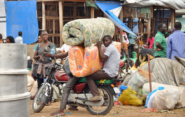 Ugandan citizens living in South Sudan ride on a motorbike with part of their belongings at a closed market serving as a temporary camp as they wait to be evacuated by the Uganda People's Defence Forces (UPDF) soldiers in Juba, South Sudan, July 15, 2016. (Photo by Jok Solomun/Reuters)