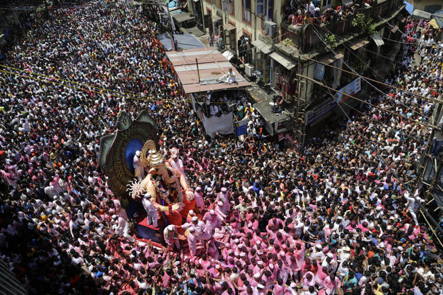 Hindu devotees participate in a procession towards the Arabian Sea with a giant idol of the elephant-headed god Ganesha to immerse it on the final day of the ten-day long Ganesha Chaturthi festival in Mumbai, India, Tuesday, September 5, 2017. (Photo by Rajanish Kakade/AP Photo)