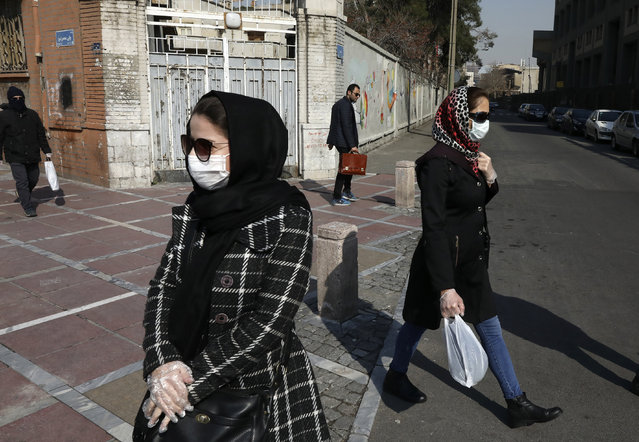 Pedestrians walk as some of them wear masks in downtown Tehran, Iran, Thursday, February 27, 2020. Amid fear and uncertainty caused by the spread of a new virus, Iranians are taking extra caution to avoid getting infected, as authorities canceled Friday prayers in Tehran, Qom and other cities. (Photo by Vahid Salemi/AP Photo)