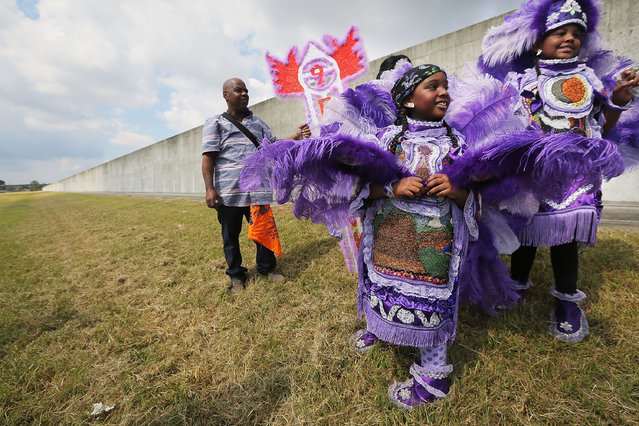 Kids are dressed in Mardi Gras Indian costumes along the repaired levee wall in the Lower Ninth Ward on the 10th anniversary of Hurricane Katrina on August 29, 2015 in New Orleans, Louisiana. (Photo by Mario Tama/Getty Images)