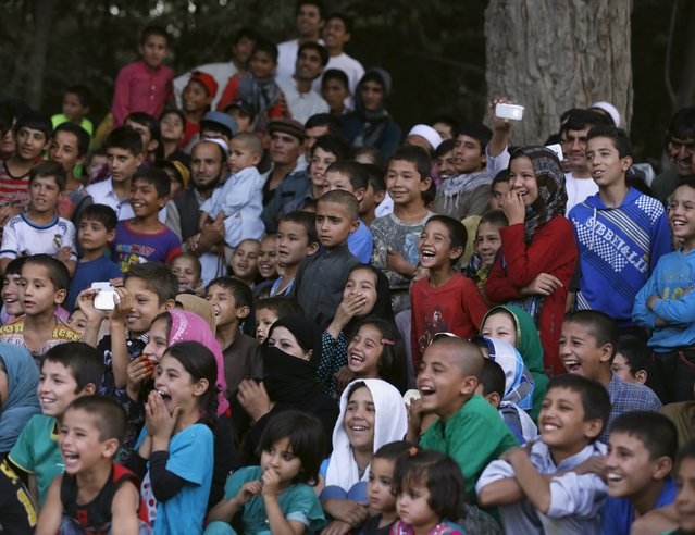 People laugh as they watch a performance by Afghan Mobile Mini Circus for Children (MMCC) during MMCC's festival in Kabul, Afghanistan August 14, 2015. (Photo by Ahmad Masood/Reuters)