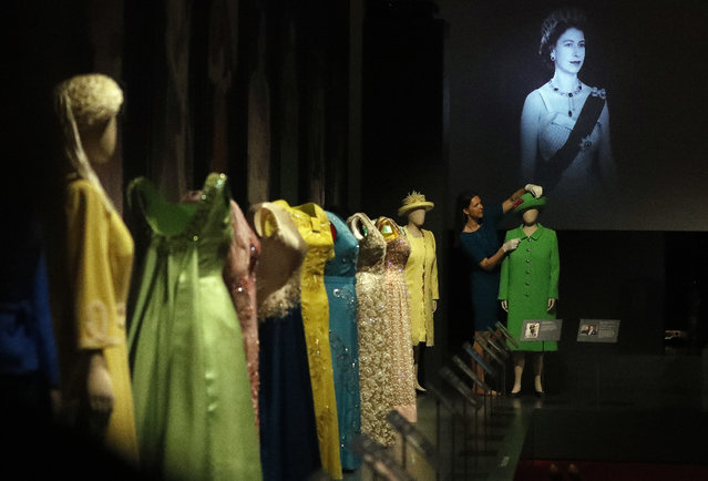 A woman adjusts dresses of Britain's Queen Elizabeth at an exhibition at Buckingham Palace in London, Thursday, July 21, 2016. (Photo by Frank Augstein/AP Photo)