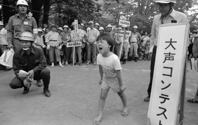 "A little boy shouts ""Earthquake!"" during a shouting contest, part of the annual evacuation drill on the National Disaster Prevention Day on September 1, 1986. The contest was aimed at teaching youngsters the importance of telling neighbors quickly and loudly of a disaster when it hits. The drill is annually conducted through out the country on the day marking the anniversary of the Great Kanto Earthquake that hit the Japanese capital and its vicinity on September 1, 1923, killing more than 104,000 people. (Photo by Sadayuki Mikami/AP Photo)"