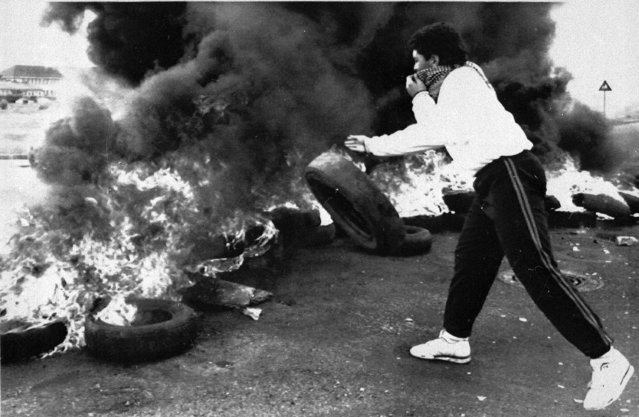 A student throws a tire onto a burning barricade outside an Athlone school in Cape Town, South Africa, September 4, 1989. Students took to the streets in protests against the pending Sept. 6 election. (Photo by Adil Bradlow/AP Photo)