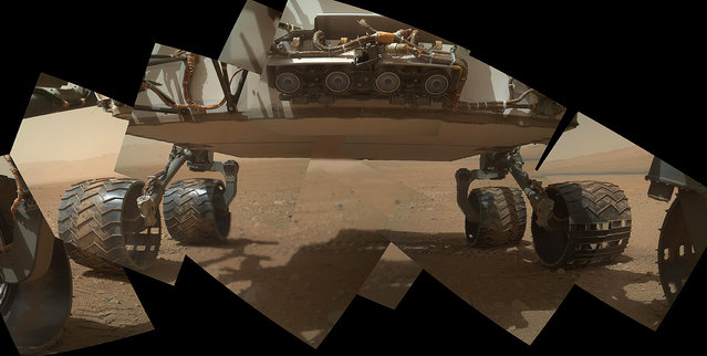 This view of the lower front and underbelly areas of NASA's Mars rover Curiosity combines nine images taken by the rover's Mars Hand Lens Imager (MAHLI) during the 34th Martian day, or sol, of Curiosity's work on Mars, on September 9, 2012. Curiosity's front Hazard-Avoidance cameras appear as a set of four blue eyes at the top center of the portrait. Fine-grain Martian dust can be seen adhering to the wheels, which are about 16 inches (40 centimeters) wide and 20 inches (50 centimeters) in diameter. The bottom of the rover is about 26 inches (66 centimeters) above the ground. On the horizon at the right is a portion of Mount Sharp, with dark dunes at its base. The camera is in the turret of tools at the end of Curiosity's robotic arm. (Photo by NASA/JPL-Caltech/Malin Space Science Systems)