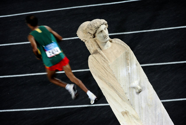 """An athlete runs past a statue during his last lap in men's marathon of Athens Olympic Games August 29, 2004. Damir Sagolj: """"Both (the) men and women's marathon of 2004 Olympic Games in Athens ended at Panathenaic Stadium, which is (a) historical old stadium that hosted many cultural and sport activities over the centuries. The stadium itself has two historical statues just where athletes are about to make the final turn before crossing the finish line and I climbed the tribune to have a clean shot of the statues and athletes. I shot (the) picture using a longer shutter speed so the athlete, the marathon runner, is blurred and the white timeless statue remained in focus"""". (Photo by Damir Sagolj/Reuters)"""