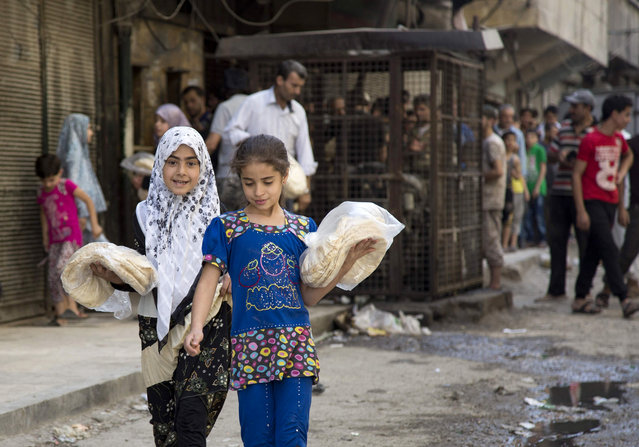 Syrian girls carry bags with bread as people queue up outisde a bakery in a rebel held neighbourhood in the northern city of Aleppo on July 12, 2016. Since mid-2012, Aleppo has been roughly divided between government control in the west and rebel control in the east, and has suffered enormous destruction in the war that has killed more than 280,000 people nationwide. Last week, a government advance brought regime troops within firing range of the Castello Road, the only remaining supply route into the opposition-held east, effectively severing rebel neighbourhoods from the outside world. With their route to the outside world cut, there is no new flour coming to the city's bakeries, and fuel to light their ovens is also now hard to find. (Photo by Karam Al-Masri/AFP Photo)