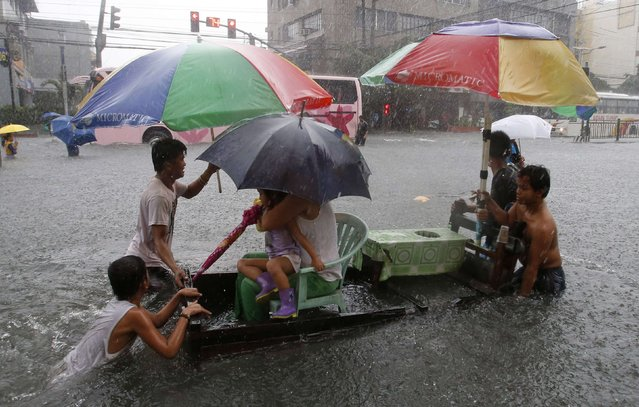 Residents are transported on an improvised cart along a flooded road as tropical storm Fung-Wong battered the Philippine capital Manila September 19, 2014. (Photo by Erik De Castro/Reuters)