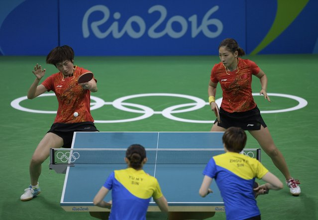 China's Ding Ning (top L) hits a shot next to China's Liu Shiwen in the women's team semi-final table tennis match against Singapore's Yu Mengyu (bottom L) and Singapore's Zhou Yihan at the Riocentro venue during the Rio 2016 Olympic Games in Rio de Janeiro on August 15, 2016. (Photo by Juan Mabromata/AFP Photo)
