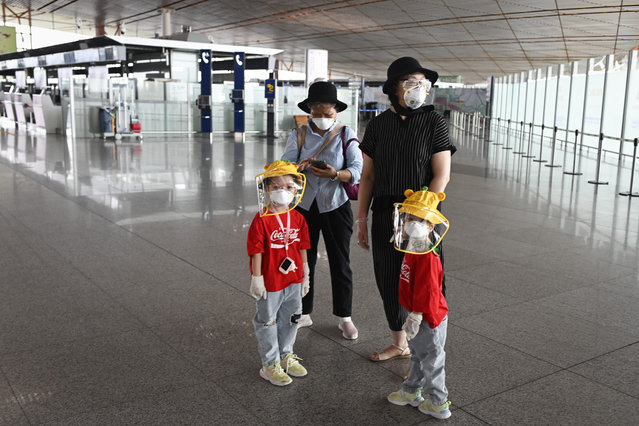 People wearing protective gear are pictured inside the terminal at Beijing's international airport on June 17, 2020. Beijing's airports cancelled more than 1,200 flights and schools in the Chinese capital were closed again on June 17 as authorities rushed to contain a new coronavirus outbreak linked to a wholesale food market. (Photo by AFP Photo/China Stringer Network)