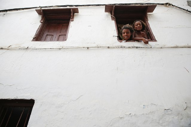 Girls look through the window of a house in Kasbah of the Udayas, a picturesque ancient part of Rabat September 21, 2014. (Photo by Damir Sagolj/Reuters)