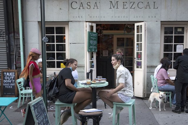 Customers dine outside Casa Mezcal, Monday, June 22, 2020, in New York. New York City ventured into a crucial stage of reopening as stores let people in Monday, offices brought workers back, restaurants seated customers outdoors and residents both welcomed and worried about rebounding from the nation's deadliest coronavirus outbreak. (Photo by John Minchillo/AP Photo)