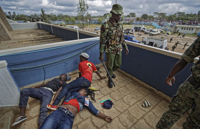A policeman stands next to supporters of Kenyan President Uhuru Kenyatta lying unconscious after being beaten by police when they tried to storm through gates to get in during Kenyatta's inauguration ceremony at Kasarani stadium in Nairobi, Kenya Tuesday, November 28, 2017. Kenyatta is being sworn in on Tuesday, ending a months-long election drama that saw the first vote nullified by the country's top court and the second boycotted by the opposition. (Photo by Ben Curtis/AP Photo)