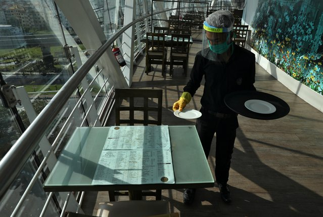 A waiter wearing a protective face mask and a shield sets a table inside the Biswa Bangla Gate restaurant, after authorities eased lockdown restrictions that were imposed to slow the spread of the coronavirus disease (COVID-19), in Kolkata, India, June 25, 2020. (Photo by Rupak De Chowdhuri/Reuters)