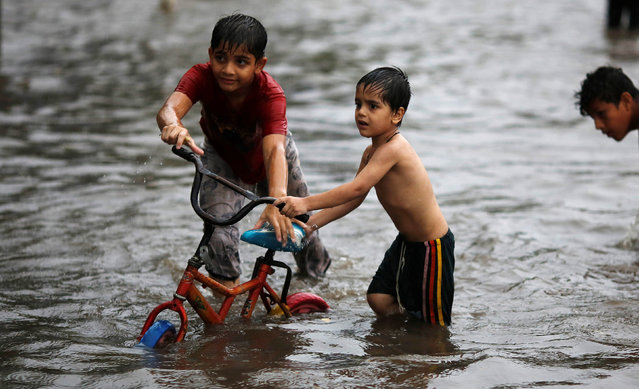 Children play on a flooded street during heavy rains in New Delhi, India, August 29, 2016. (Photo by Adnan Abidi/Reuters)