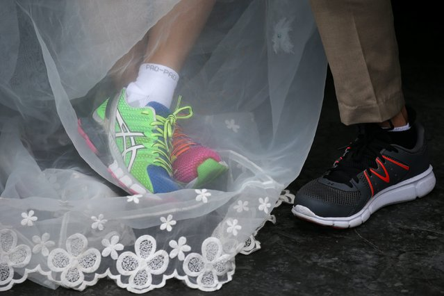 """A couple dons their running shoes  during the """"Running of the Brides"""" race, in Bangkok, Thailand, December 2, 2017. (Photo by Athit Perawongmetha/Reuters)"""