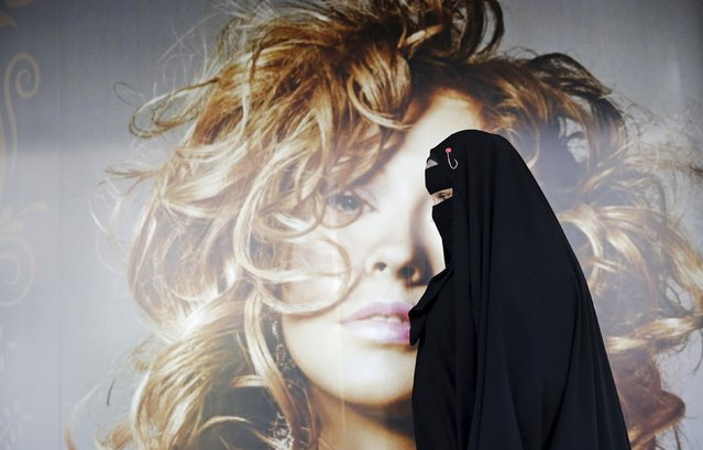 Gisele Marie, a Muslim woman and professional heavy metal musician, walks past a poster after a rehearsal at her house, in Sao Paulo September 15, 2015. (Photo by Nacho Doce/Reuters)
