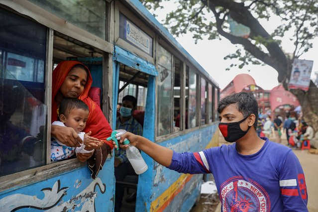 A man sprays hand sanitizer to a child who is traveling on a public bus amid the coronavirus disease (COVID-19) outbreak in Dhaka, Bangladesh, June 22, 2020. (Photo by Mohammad Ponir Hossain/Reuters)