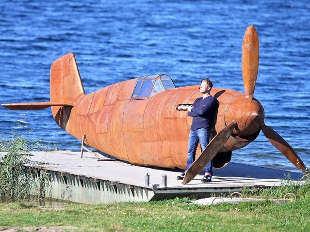 Artist Raik Dalgas stands by his anti-war sculpture on the banks of the Goitzsche in Bitterfeld-Wolfen, Germany, 15 October 2014. His rusty work, which is nine and half meter long and weighs one tonne, is in the form of a historic war plane. A sculpture park will be erected by the lake in the coming year. (Photo by Jan Woitas/EPA)