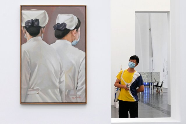 """A man wearing a face mask amid concerns of the COVID-19 coronavirus stands next to """"Just Like in the Mirror 2"""" by Zhang Hui as he visits the exhibition """"Meditations in an Emergency"""" at UCCA Center for Contemporary Art in Beijing on June 13, 2020. (Photo by Wang Zhao/AFP Photo)"""