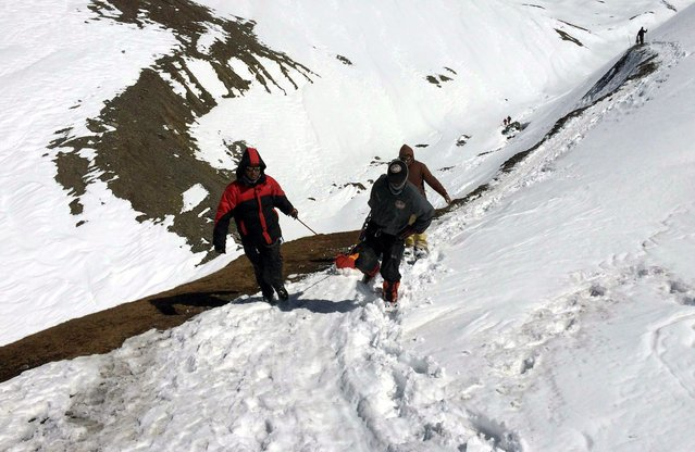 A handout picture made available by the Nepalese Army shows members of the army pulling the body of a trekker from the Thorung La mountain pass on the Annapurna Circuit, near Muktinath, in Mustang district, Nepal, 17 October 2014. In total seven dead bodies of trekkers including from Poland, Israel, China and Nepal have been brought to Kathmamdu over the past 24 hours, however the search operation continues for trekkers who went missing in a snowstorm, triggered by Cyclone Hudhud which brought heavy snowfall, which has so far claimed to lives of 29 people, though dozens remain unaccounted for. (Photo by EPA/Nepalese Army)