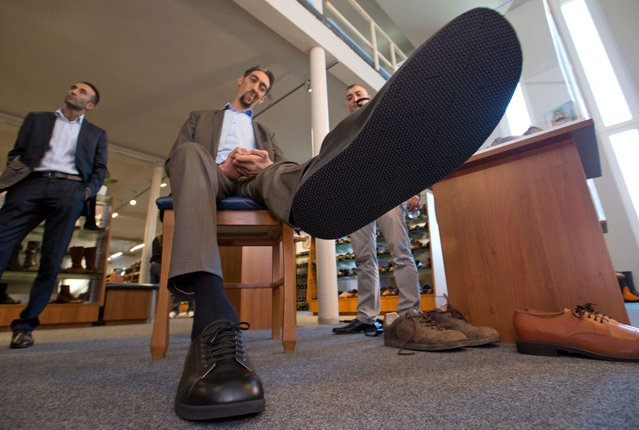 Sultan Koesen (C), the world's tallest person at 2.51 metres, shows off his new shoes in Vreden, Germany, 29 September 2015. He wears custom-made size 60 footwear made by Wessels shoemakers, who cater specially for extra-large feet. (Photo by Friso Gentsch/EPA)