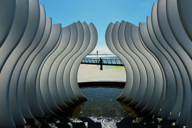 A man walks by a sculpture at the seafront promenade on July 27, 2020 in Qingdao, Shandong Province of China. (Photo by Wang Haibin/VCG via Getty Images)