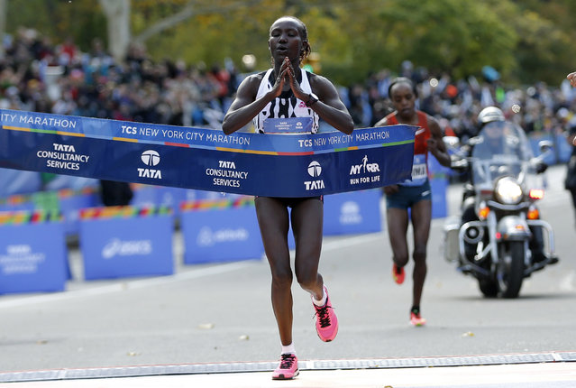 Mary Keitany of Kenya crosses the finish line to win the women's professional division. At right is second place finisher Jemima Sumgong of Kenya. (Photo by Mike Segar/Reuters)