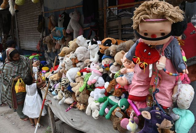 A woman along with her daughter looks at toys at a roadside stall in Lahore on August 23, 2020. (Photo by Arif Ali/AFP Photo)