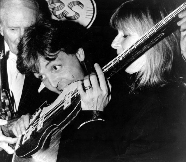 Fomer Beatle Paul McCartney bites into a 4-string bass guitar cake during a luncheon at Claridge's in London, England, Tuesday, December 20, 1989. McCartney received a Performing Right Society Award, held by an unidentified man at left, in recognition of his unique contribution to British music. At right is Linda McCartney. (Photo by AP Photo)