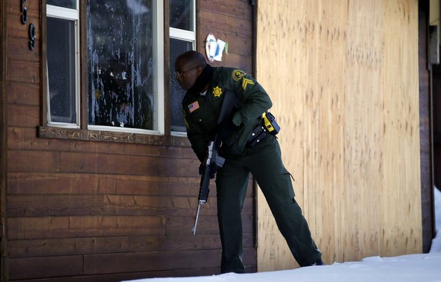 San Bernardino County Sheriff's officer Ken Owens searches a home for former Los Angeles police officer Christopher Dorner in Big Bear Lake on February 10, 2013. The hunt for Dorner, suspected in three killings, entered its fourth day, a day after the police chief ordered a review of the disciplinary case that led to the fugitive's firing and new details emerged of the evidence he left behind. (Photo by Jae C. Hong/Associated Press)